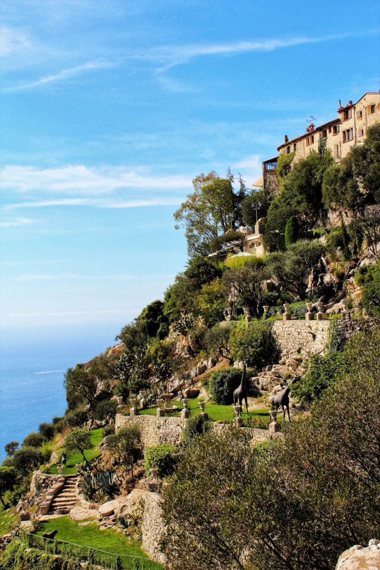 "One of the most beautiful hilltop villages in the south of France is Eze. Perched in an ""eagle's nest"" fashion, this village can be viewed from afar due to its ochre colour church and botanical hillside garden filled with interesting statues, cacti and tropical plants."