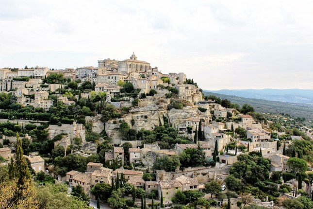 This hilltop photogenic village offers one of the most stunning panoramic views of the Luberon valley. The buildings of pale beige or gray stone spiral around the rock on which the village stands. Walk along the ancient cobblestone streets next to the soaring high stone houses with their pale blue and mint green shutters. It is popular for a reason.