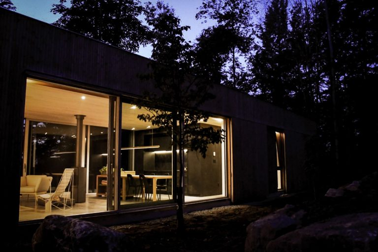 The modern Hinter House sits up high quietly behind the treetops. | Escape to the Hinter House in The Laurentians, Canada